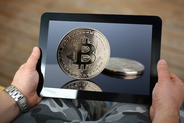 De tablet van de mensenholding met bitcoin imag
