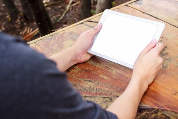 De tabletcomputer van de close-up op aziatische mensenhand op houten lijst geweven achtergrond met exemplaar spac