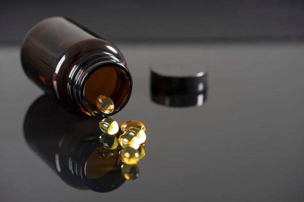 De tabletten liggen op een gespiegelde zwarte achtergrond, reflecteren erin. donkere fles met medicijnen onscherp.