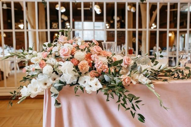 De tafel decoreren met bloemen en stof voor een huwelijksceremonie in banket