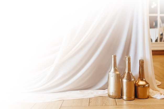 De tafel decoreren met gouden flesvazen en stof voor een bruiloftsbanket