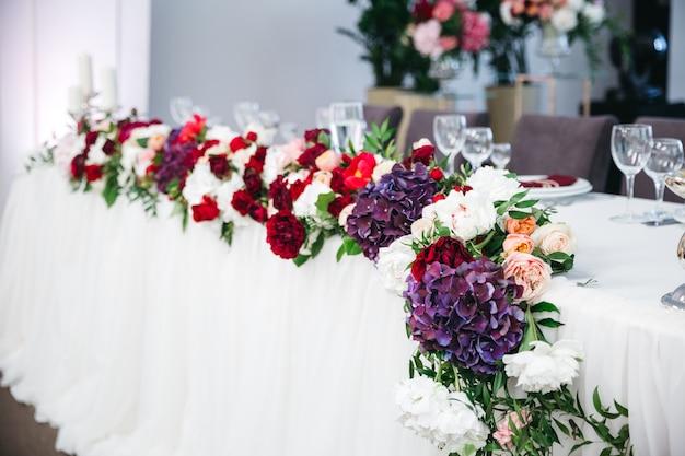 De tafel versieren van veel gekleurde bloemen