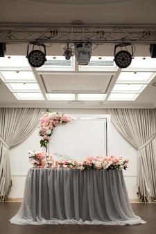 De tafel voor de pasgetrouwden is versierd met verse bloemen in het restaurant. vierkante verlichting en schijnwerpers