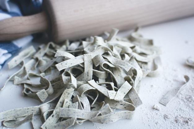 De tagliatelle van deegwaren die door bloem met een houten rol op een witte achtergrond wordt behandeld