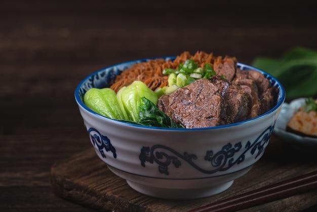 De taiwanese beroemde noedel van het voedselrundvlees met gesneden gestoofde rundvleessteel, pens en groenten op houten lijstachtergrond.