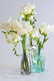 De tak van witte fresia's met bloemen en knoppen in decoratieve flessen