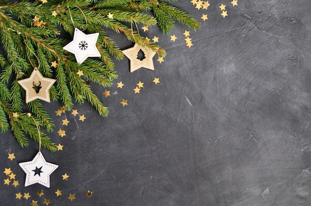 De takken, houten sterdecoratie, gouden confetti op donker