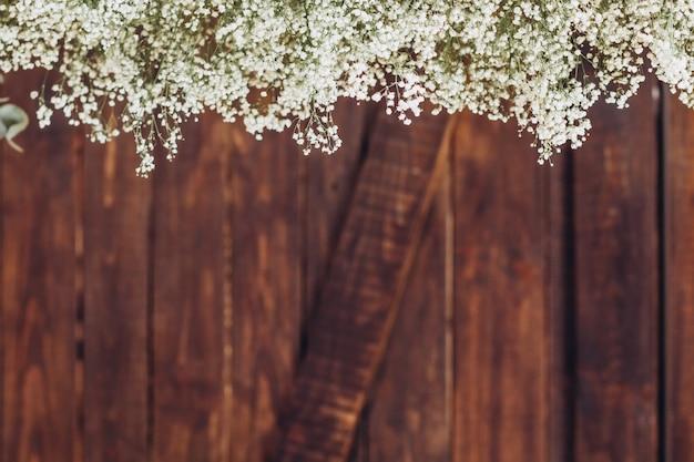 De takken van witte bloemen op een donkere houten achtergrond.
