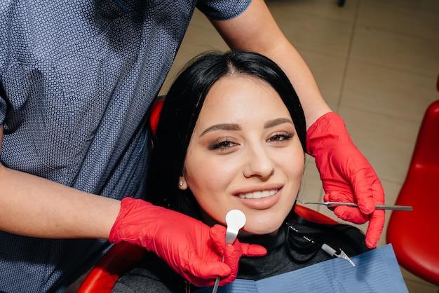 De tandarts behandelt de tanden van het meisje aan de patiënt. tandheelkunde. detailopname.