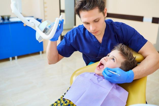 De tandarts die de tanden van jongenstiener controleert in het kantoor van de tandarts.