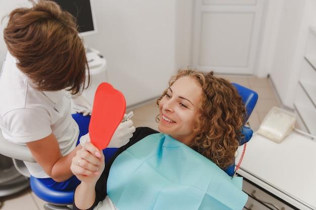 De tandarts die de tandkleur van de patiënt vergelijkt met monsters voor een bleekbehandeling