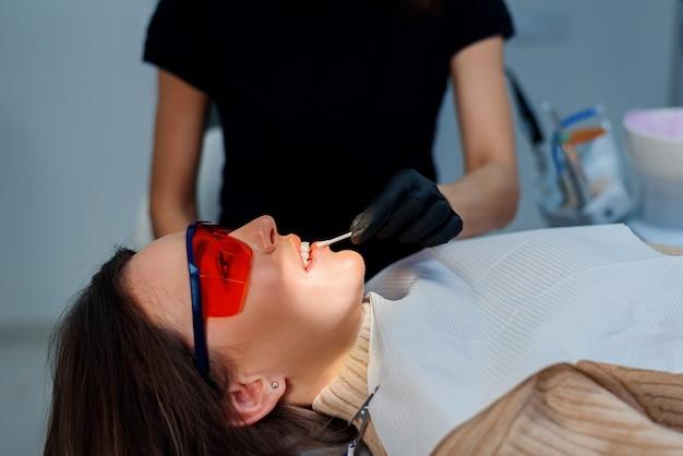 De tandarts gebruikt een wattenstaafje om de lippen van de meisjespatiënt te smeren, om de perceptie van verdere procedures te vergemakkelijken.