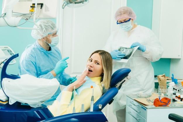 De tandarts legt de details van de röntgenfoto uit aan zijn collega, de patiënt is verrast door wat er gebeurt.