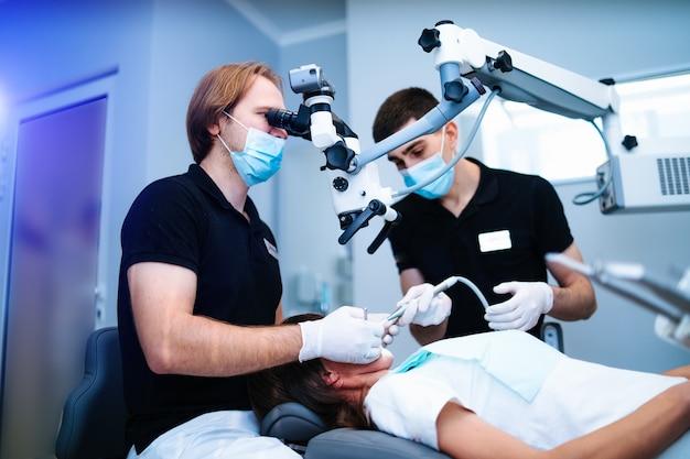 De tandarts onderzoekt het gebit van de patiënt met een tandmicroscoop.