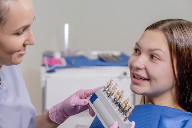 De tandarts probeert de juiste kleur te kiezen voor de tandimplantaten