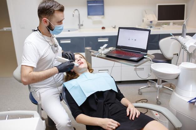 De tandarts scant de tanden van de patiënt met een 3d-scanner.