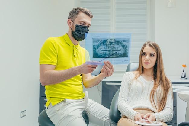 De tandarts toont een foto van een röntgenfoto van de tanden van de patiënt in een moderne tandheelkundige kliniek legt uit en onderzoekt de behandeling met een röntgenfoto mannelijke specialist legt opties uit aan jonge vrouw