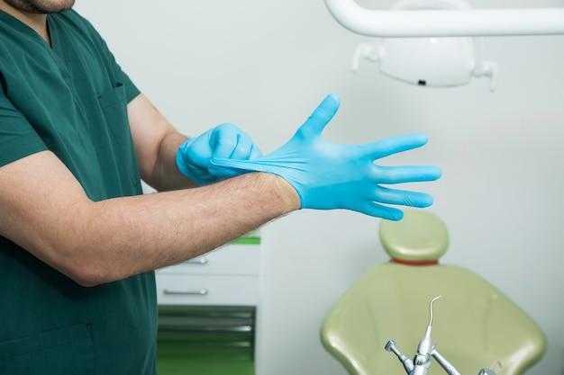 De tandarts trekt voor het werk handschoenen aan