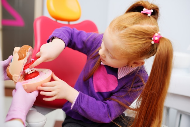 De tandarts vertelt het kind over mondhygiëne