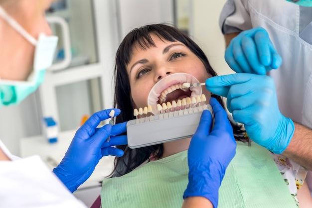 De tanden van de patiënt vergelijken met de sampler in de handen van de arts