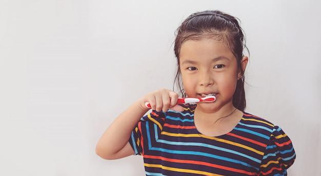De tanden van weinig aziatische leuke meisjesborstel