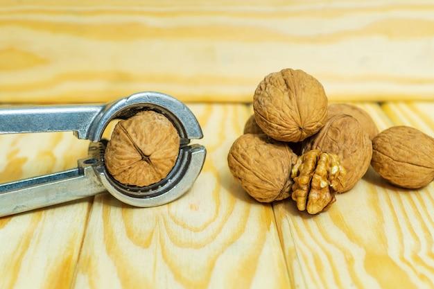 De tang hakt noten op een oude houten lijst alvorens te koken