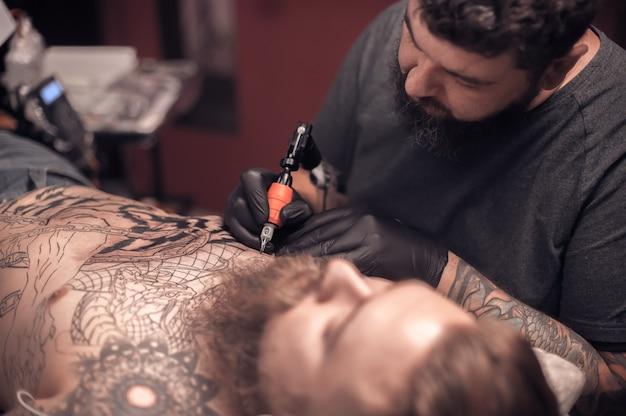 De tattoo-specialist demonstreert het proces van het krijgen van tatoeages in een tattoo-salon.