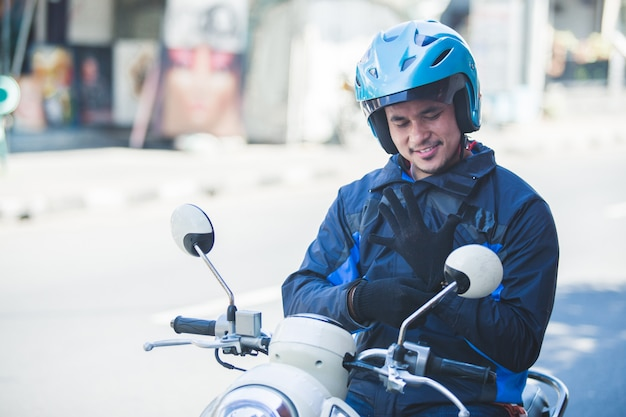 De taxichauffeur die van de motorfiets zijn handschoenen draagt voor veiligheid het berijden
