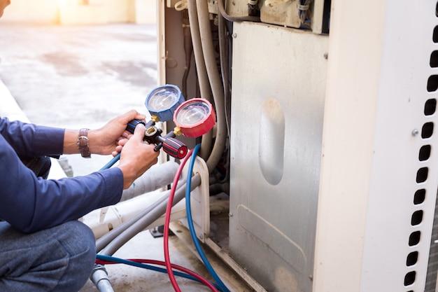 De technicus controleert airconditioner, meetapparatuur die airconditioners vullen.