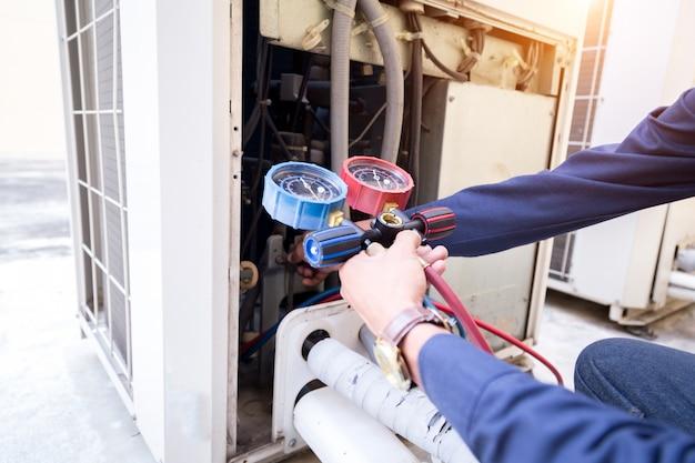 De technicus controleert airconditioner, meetapparatuur voor het vullen van airconditioners.