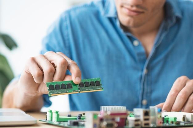 De technicus die een ram-geheugen instelt op de aansluiting van het moederbord van de computer