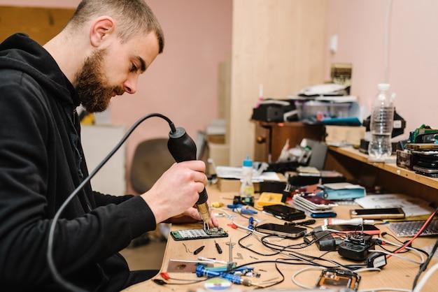 De technicus die het smartphonemotherboard in het laboratorium herstelt. concept van computer hardware, mobiele telefoon, elektronische reparatie, upgrade, technologie. mens die proces van telefoonreparatie in workshop tonen.