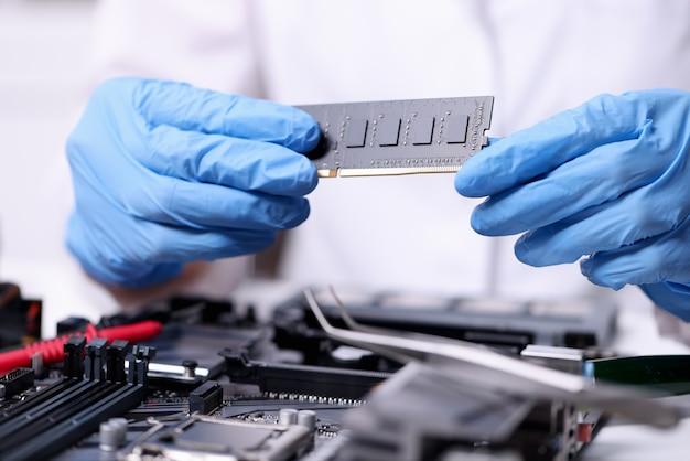 De technicus dient rubberhandschoenen in die de close-up van de computersram houden. laptop reparatie- en onderhoudsconcept