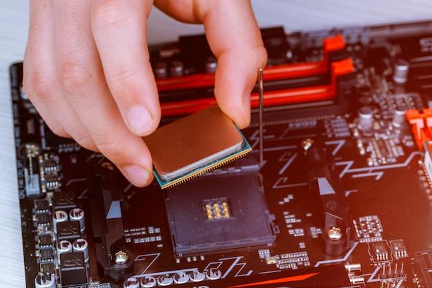 De technicus plaatst de cpu op de aansluiting van het moederbord van de computer.