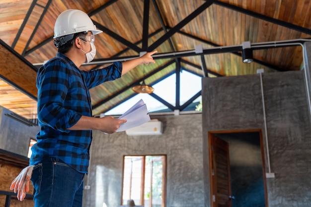De technicus van de bouwingenieur inspecteert de structuur onder het dak bij bouwwerf