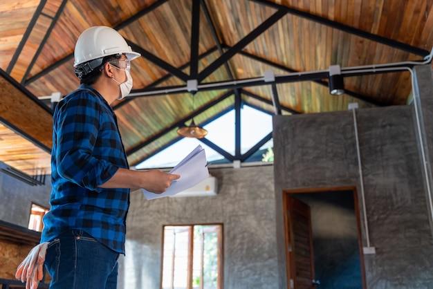 De technicus van de bouwingenieur inspecteert de structuur onder het dak op de bouwplaats of de bouwplaats van een huis.