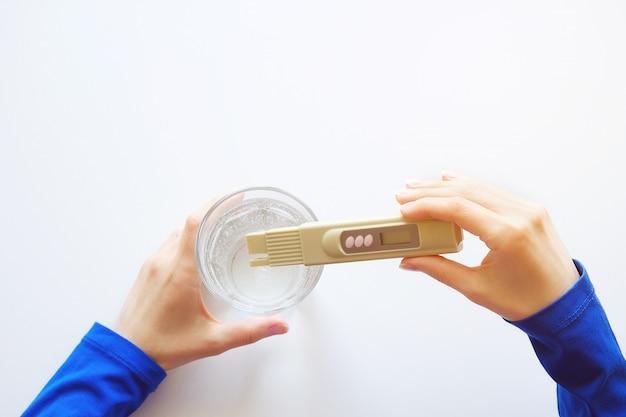 De technicus van het meisjeslaboratorium houdt een digitale tester vast om de waterkwaliteitscontrole te bepalen.
