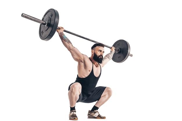 De techniek van het doen van een oefening van deadlift met een halter van een gespierde, sterke, getatoeëerde, bebaarde sportman