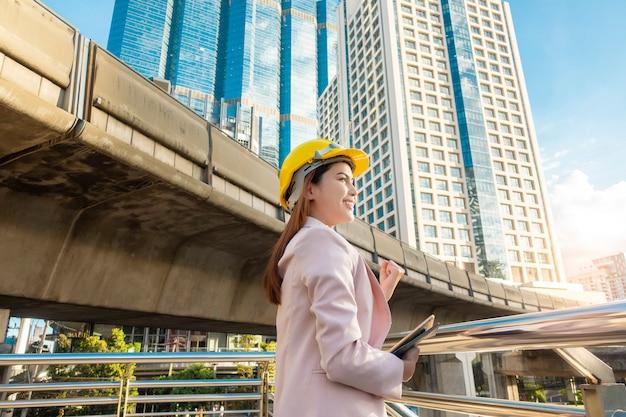 De techniekvrouw werkt op openluchtstadsachtergrond