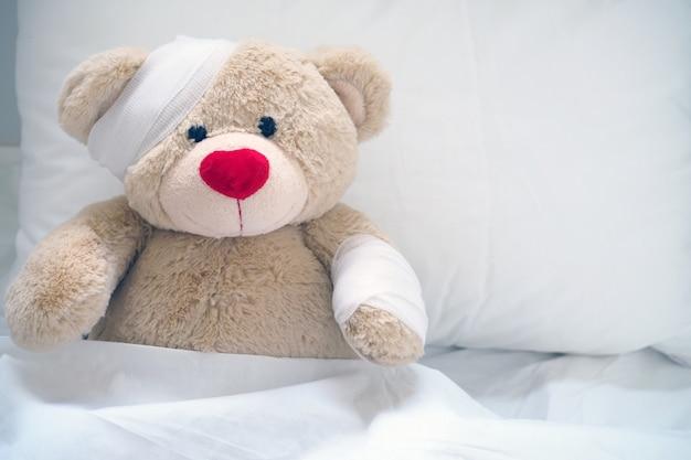 De teddybeer heeft gaas op het hoofd