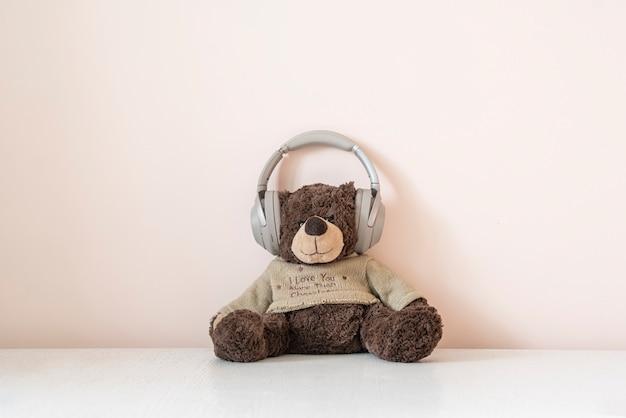 De teddybeer in hoofdtelefoons luistert naar de audiomuziekradio