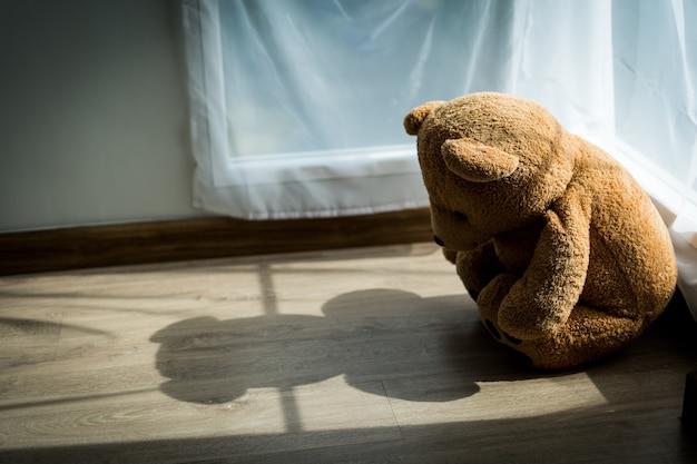 De teddybeer kijkt verdrietig en teleurgesteld in de hoek van de kamer waar zacht zonlicht doorheen valt. poppen met depressie of psychische aandoeningen. kinderziekte of ziekteconcept