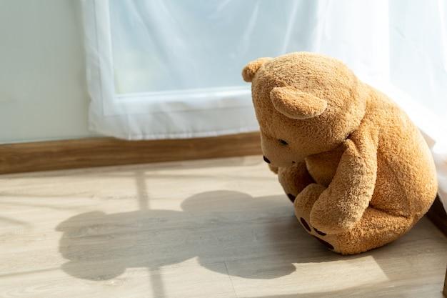 De teddybeer zag er verdrietig en teleurgesteld uit terwijl hij in de hoek van de kamer zat