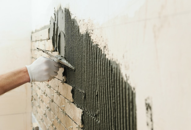 De tegels op de muur installeren.