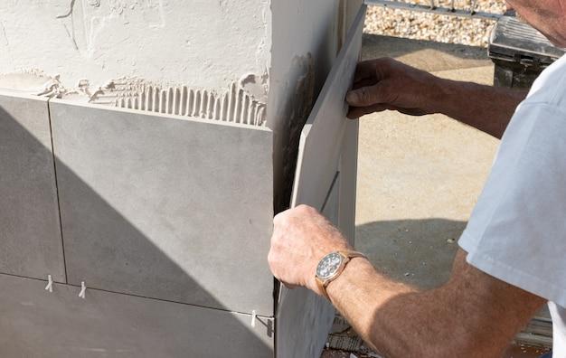 De tegelzetter legt een keramische tegel op de muur