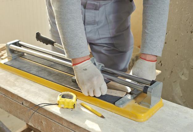 De tegelzetter snijdt een keramische tegel met een snijmachine.