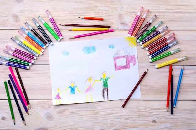 De tekening is gemaakt door een kind met behulp van gekleurde stiften en potloden. kindertekening van een gezin, ouders, kinderen en thuis. een blije familie. tekening van kinderen