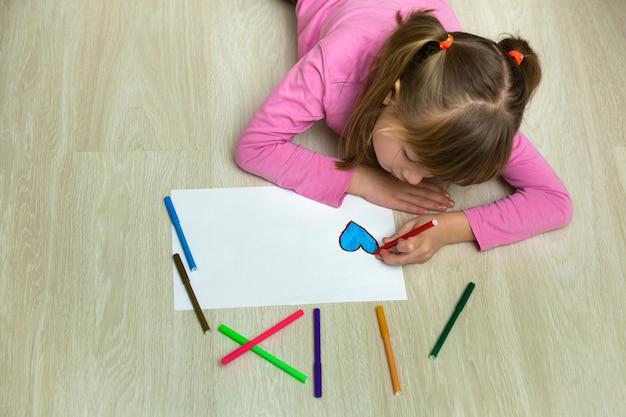 De tekening van het kindmeisje met kleurrijke potloden schetst hart op witboek. kunstonderwijs, creativiteit concept.