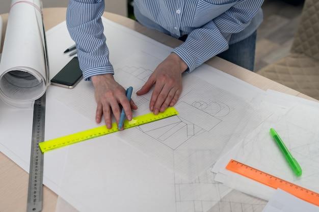 De tekening van het nieuwe ontwerp, handen met een potlood en een liniaal