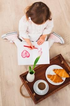 De tekeningshart van het meisje dichtbij dienblad met koffie